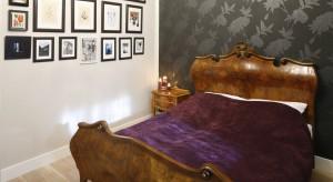 Drewniane łóżko o klasycznych kształtach dodaje sypialni charakteru. W połączeniu z wyrazistą, ciemną tapetą i oryginalną domową galerią powstało spójne, ponadczasowe wnętrze.<br /><br />