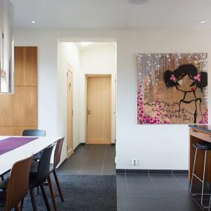 Podłogę w kuchni wykończono grafitową okładziną, kontrastującą z białymi ścianami i jasnym stołem w jadalni, za to korespondującą z ciemnym blatem kuchennym. Fot. Per Jansson.