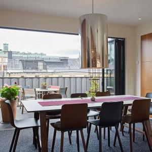 Duże harmonijkowe drzwi balkonowe w jadalni po otwarciu odsłaniają panoramiczny widok na okolicę. Brak progu w drzwiach tworzy wrażenie przenikania się przestrzeni jadalni z balkonem. Fot Per Jansson.