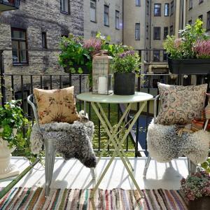 Skąpany w słońcu balkon po stronie południowej budynku zachęca do leniwego relaksu. Wzorzyste tekstylia i bogato rozmieszczona roślinność  nadają mu domowego, przytulnego charakteru. Fot. Alvhem Makleri.
