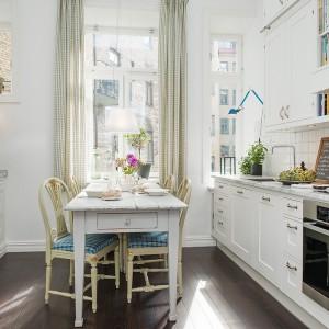 Białą, jasną kuchnię dodatkowo rozświetla światło dzienne, wpadające do wnętrza przez wysokie okna. Zlokalizowany przy oknie stolik to idealne miejsce na poranna kawę i energetyzujące śniadanie przy promieniach słońca. Kontrastującym akcentem jest ciemna drewniana podłoga. Fot. Alvhem Makleri.