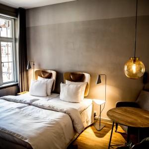 We wnętrzach pokoi dla gości panuje industrialny klimat. Szare ściany, surowe oświetlenie i oszczędne dekoracje przemawiają do zwolenników minimalistycznych form. Fot. Brochner Hotels.