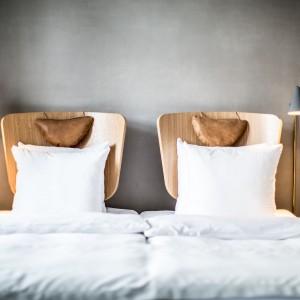 Łóżka w pokojach dla gości utrzymano w ciekawej stylistyce. Zagłówki mają formę przywodzącą na myśl oparcia krzeseł. Kolor ciepłego drewna kontrastuje i wybija się na tle surowej, szarej ściany. Fot. Brochner Hotels.