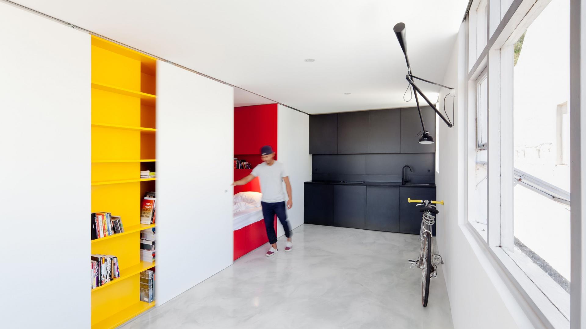 Za przesuwnymi białymi drzwiami ukryto, wykończoną na czerwono, sypialnię. Po zamknięciu drzwi chowa się ona w ścianę, a przy otwartych drzwiach nadaje wnętrzu koloru i przytulniejszego charakteru. Fot. Nicholas Gurney.