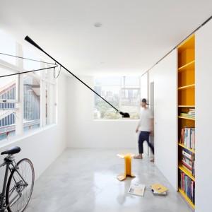 Poprowadzone pod sam sufit duże okna i dominująca we wnętrzu biel nadają studiu wrażenia przestrzenności. Długa czarna lampa kontrastuje z jasnymi barwami i stanowi przykuwający wzrok akcent dekoracyjny w tym minimalistycznym mieszkaniu. Fot. Nicolas Gurney.