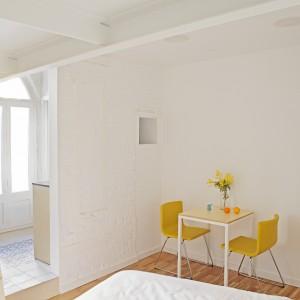Dostęp do półpięter zapewniają drewniane drabiny, komponujące się wizualnie z podłogą. Fot. Asier Rua.