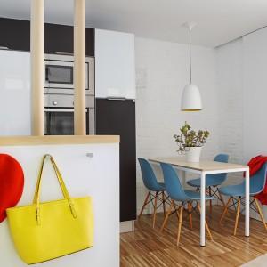 W rogu kuchni zlokalizowano niewielki stół, pełniący funkcję jadalni. Monochromatyczną kolorystykę pomieszczenia ożywiono niebieskimi krzesłami. Fot. Asier Rua.