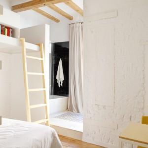 We wnętrzu zachowano elementy oryginalnego wykończenia mieszkania. Biała cegła na ścianie kontrastuje z nowoczesną stylistyką mebli i stanowi ciekawy, rustykalny akcent dekoracyjny. Fot. Asier Rua.