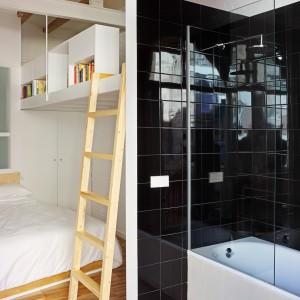 Wykończona czarnymi płytkami przestrzeń kąpielowa w łazience kontrastuje z dominującymi w mieszkaniu jasnymi barwami i stanowi elegancki, surowy akcent. Fot. Asier Rua.