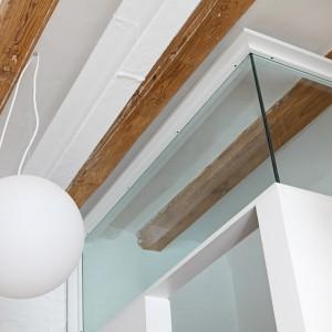 Pod sufitem pozostawiono odsłonięte drewniane belki stropowe, dodatkowo wyeksponowane przez otaczającą je biel. Komponują się idealnie z drewnianymi elementami wykończenia wnętrza oraz nadają mieszkaniu lekko skandynawskiego charakteru. Fot. Asier Rua.