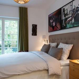 Na parterze, położona za salonem znajduje się duża sypialnia małżeńska z bezpośrednim dostępem do ogrodu. Wnętrze jest przytulne i eleganckie, a uwagę przyciąga duży tekstylny zagłówek. Fot. Per Jansson.