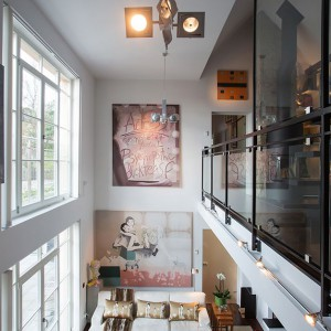 Sufit w salonie sięga na wysokość blisko 6 metrów, umożliwiając lokalizację okien na bardzo wysokiej ścianie. Przeszklona powierzchnia zapewnia bogaty dostęp dziennego światła, docierającego na dwie kondygnacje. Fot. Per Jansson.