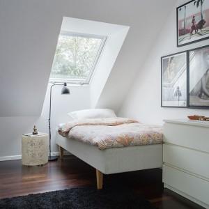 Urokliwa niewielka sypialnia na piętrze. Z łóżka umiejscowionego bezpośrednio pod oknem dachowym można obserwować gwiazdy przed zaśnięciem. Głównym akcentem dekoracyjnym w pokoju są liczne oprawione zdjęcia na ścianie. Fot. Per Jansson.