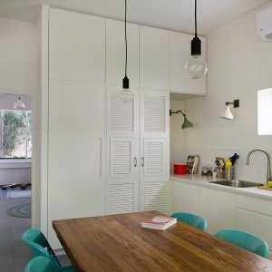 Stylizowany drewniany stół i nowoczesne krzesła, choć pozornie do siebie nie pasują, w połączeniu tworzą perfekcyjny duet. Turkusowe krzesła pięknie ożywiają również przestrzeń kuchni. Fot. Galit Deutsch.