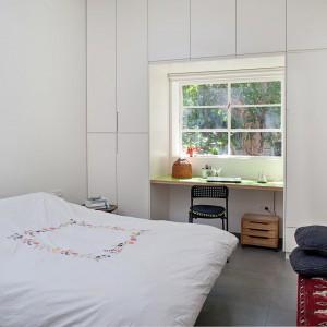 Folklorystyczny motyw powtarza się także na łóżku. Duże okno pięknie doświetla przestrzeń sypialni. Fot. Galit Deutsch.