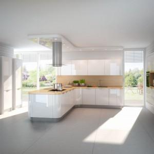 Półwysep z zainstalowaną kuchenką i wmontowanymi szafkami kuchennymi. W dużej otwartej przestrzeni jasnej kuchni, półwysep pełni funkcję wydzielającą komunikację, prowadzącą do ogrodu. Fot. Nolte Küchen, kolekcja Nova Lack.