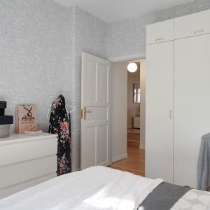 Delikatna, szara tapeta doskonale komponuje się z białymi drzwiami, meblami oraz tkaninami. Fot. Alvhem Mäkler.