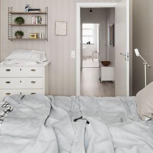 Tapeta o delikatnym wzorze rozjaśnia niewielką sypialnię. Fot. Fantasict Frank.