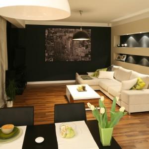 W niewielkim apartamencie elegancki, jasny narożnik stanowi główny element dekoracyjny otwartego na kuchnię salonu. Dosunięty do ścian pozwala w pełni cieszyć się niedużym metrażem wnętrza. Projekt: Lucyna Kołodziejska. Fot. Bartosz Jarosz.