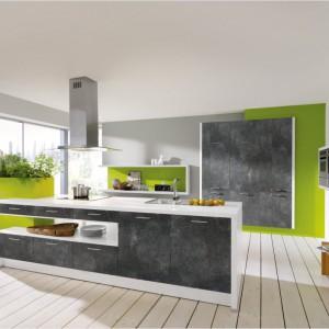Białe meble kuchenne z matowymi, grafitowymi frontami oraz drewniana jasna podłoga stanowią idealną bazę dla soczystego limonkowego akcentu na ścianie i donicy. Fot. Wellmann, meble z programu Aura.