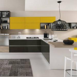 Soczyste żółte fronty wiszących szafek kuchennych i komody w takiej samej kolorystyce zostały pięknie wyeksponowane przez otaczające je czerń, biel i ciepły kolor drewna. Fot. Febal Cucine, meble z kolekcji Sand.
