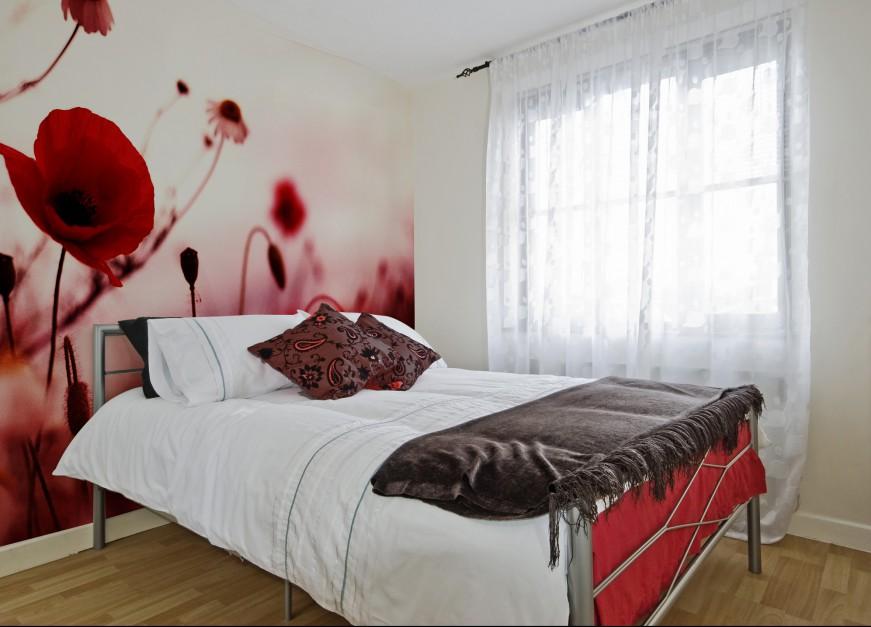 Fototapeta w czerwone maki stanowi ciekawy, dominujący akcent we wnętrzu. Przy użyciu tak wyrazistego wzoru pozostałe ściany w sypialni powinny pozostać bardzo jasne. Fot. Art of wall.