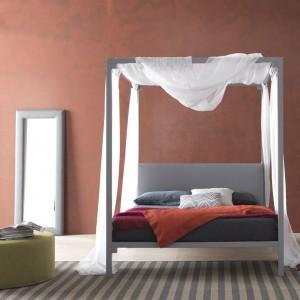 Stonowana, ceglana czerwień dobrze komponuje się z delikatną formą łóżka z baldachimem. Fot. Bolzan Letti.
