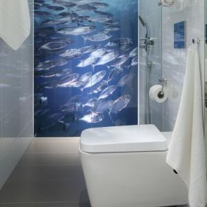 Głównym elementem dekoracyjnym w tej niewielkiej, gościnnej toalety jest fototapeta. Motyw ławicy ryb pięknie zdobi całą ścianę we wnęce prysznicowej. Ze względów praktycznych zabezpiecza ją tafla hartowanego szkła. Projekt: Anna Maria Sokołowska. Fot. Bartosz Jarosz.