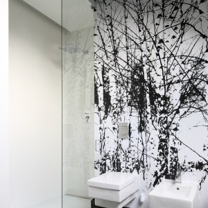 Brzozowy las to motyw dekoracyjny na fototapecie, którą wykończona została ściana za sanitariatami. We wnętrzu urządzonym w bieli i czerni takie zdjęcie prezentuje się świetnie. Projekt: Dominik Respondek. Fot. Bartosz Jarosz.