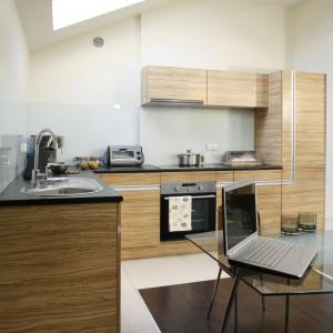 Posadzkę w kuchni wykonano w dwóch kolorach. Podłoga wyznaczająca miejsce stołu jest ciemnobrązowa, podczas gdy linię obudowy kuchennej zaznaczono białym kolorem. Projekt: Katarzyna Merta-Korzniakow. Fot. Monika Filipiuk-Obałek.