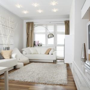 Niewielki salon zaaranżowany został w subtelnej bieli. Ocieplają ją elementy drewniane, takie jak podłoga czy panel telewizyjny. Projekt: Małgorzata Mazur. Fot. Bartosz Jarosz.