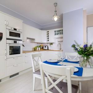 Przestrzeń jadalni umownie zaznaczono tapetą na ścianie. Jej pionowe biało-niebieskie pasy pasują kolorystycznie do aranżacji stołu. Fot. Decoroom.