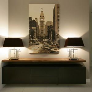 Do białego przedpokoju wstawiono brązową szafkę, na której ustawiono dwie stylowe lampy. Fot. Svoya studio.