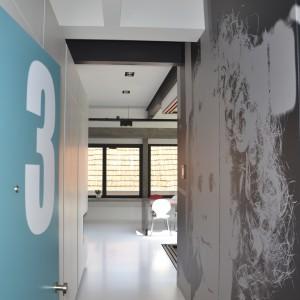 Kolorowe akcenty ożywiają wnętrze - tutaj za pomocą turkusowej powierzchni drzwi w przedpokoju. Przeciwległą ścianę pokryto wielkoformatową fototapetą ze zdjęciem córeczki architektów. Fot. Aeon Architecten.