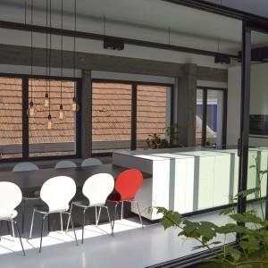 """Dwie przeciwległe ściany przestrzeni kuchni i jadalni pokryto wielkowymiarowymi przeszkleniami. Duże, przesuwne okna zapewniają niemal nieograniczony dostęp dziennego światła do wnętrza """"na przestrzał"""". Fot.  Aeon Architecten."""
