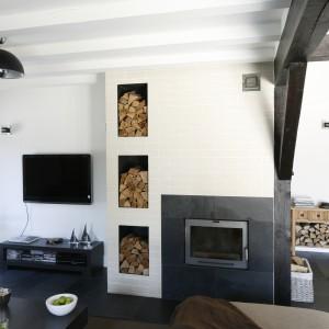 Ciepłym akcentem we wnętrzu jest urokliwy kominek, obłożony - podobnie jak podłoga na parterze - łupkiem kamiennym. Ścianę w najbliższym sąsiedztwie obłożono białym klinkierem. Odsłonięte wnęki na przechowywanie drewna nadają aranżacji swojskiego klimatu. Fot. Bartosz Jarosz.