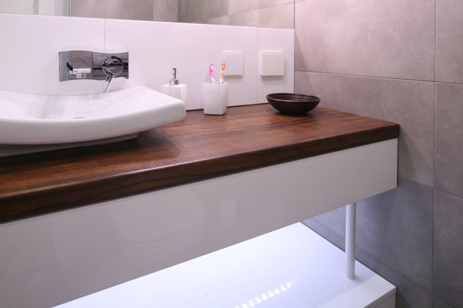 Minimalistyczą łazienkę, której surowy charakter to w dużej mierze zasługa szarych płytek gresowych (Nowa Gala), ociepla laminowany blat w ciemnym dekorze drewna. Fot. Bartosz Jarosz.