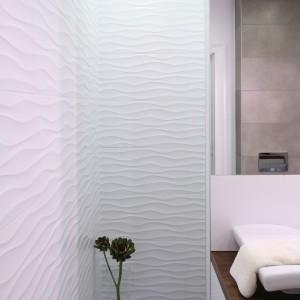 Płytki marki Aparici z falującym dekorem zdobią ściany strefy kąpielowej. Prysznic umieszczono we wnęcę jednak nie zamkniętej drzwiami. Otwarta forma, jednolita podłoga w całej łazience oraz odpływ prysznicowy w posadzce spełniają wymogi nowoczesnego urządzania. Fot. Bartosz Jarosz.