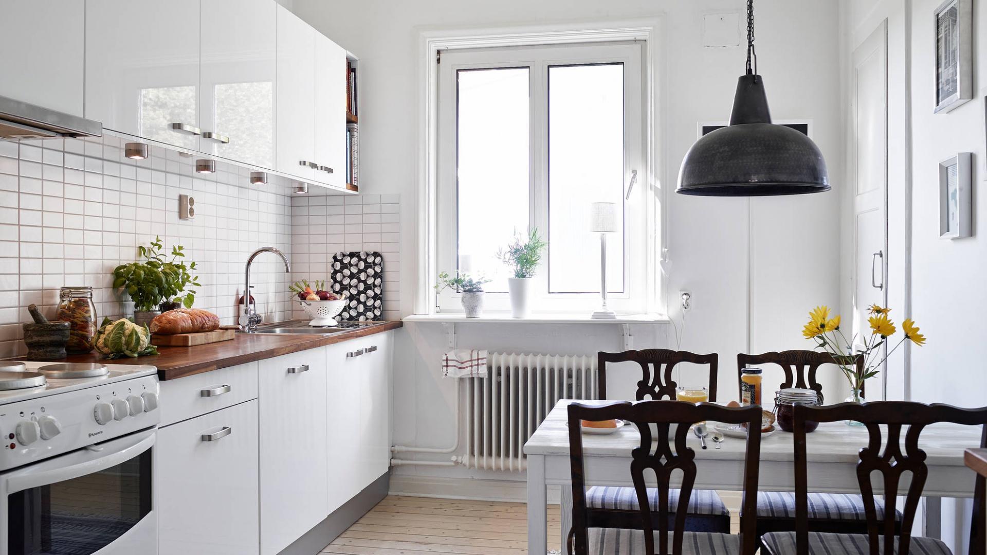 W kuchni ścierają się ze sobą dwa odmienne style. Klasyczne białe kafle, drewniany blat oraz stylizowane krzesła nadają pomieszczeniu tradycyjnego, delikatnie rustykalnego charakteru. Z kolei industrialna czarna lampa i gładkie fronty szafek na wysoki połysk to ukłon w stronę nowoczesnej stylistyki. Fot. Stadshem.