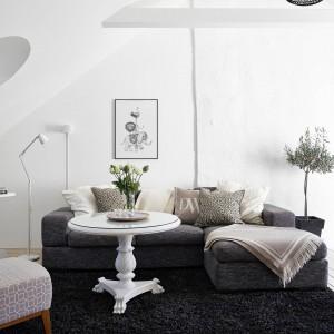W salonie dominującymi kolorami są biel i czerń, przechodząca w różne odcienie szarości. Cieplejszym akcentem są beżowe tekstylia, którymi udekorowany został komplet wypoczynkowy. Na tle ciemnego dywany, wzrok przyciąga barokowy biały stoli kawowy. Fot. Stadshem.