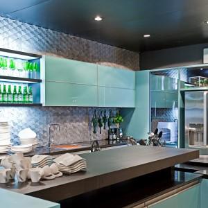 Mozaika na ścianie w kuchni to klasyka gatunku. Tutaj przyjęła formę pięknych marmurowych płytek o trójwymiarowej, pofalowanej fakturze. Stanowią efektowne tło dla turkusowych szafek. Fot. Mosarte, kolekcja Arte Moderna.