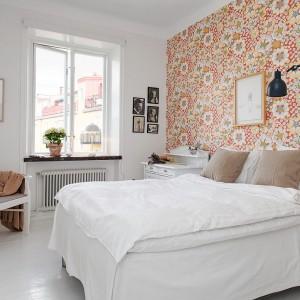 Kolorowa, bogato dekorowana tapeta dobrze wygląda umieszczona tylko na jednej ścianie. Pozostałe ściany pomalowano na biało, dzięki czemu wyrazisty wzór nie przytłacza wnętrza sypialni, a nadaje jej oryginalny klimat. Fot. Alvhem Mäkler.