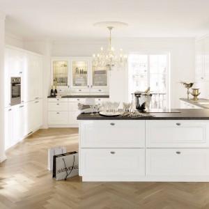 Jasna przestrona kuchnia z półwyspem. Efektywne klasyczne meble wykończono na połysk, nadając pomieszczeniu efekt glamour. Białe meble wieńczy ciemny blat kuchenny. Fot. Alno AG, program Alnopol.