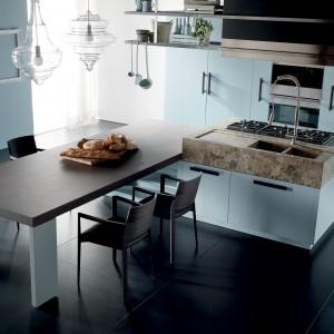 Białe szafki kuchenne, wyspa z efektownym kamienym blatem i połączony z nią kuchenny stół. Propozycja eleganckiej, stylowej kuchni, gdzie każdy element ma swóją funkcję. Praktyczne rozwiązania zamknięto w piękną formę. Fot. Toncelli, model Nantia.