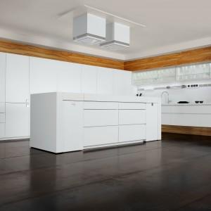 Nowoczesne białe meble z minimalistycznymi gładkimi frontami. Ich sterylny wygląd ocieplają wstawki w kolorze naturalnego drewna. Jasna wyspa i obudowa kontrastują efektownie z ciemną podłogą. Fot. Toncelli, kolekcja Essential Quadra.