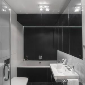W przeciwieństwie do reszty pomieszczeń w mieszkaniu, gdzie zastosowano wiele barw, w łazience postawiono na monochromatyczną czarno-białą kolorystykę. Białe i czarne płytki o dużym formacie podkreślają nowoczesny charaker wnętrza. Płytki na ścianie za umywalką pokryte są delikatną, trójwymiarową fakturą i subtelnie przyzdabiają minimalistyczne wnętrze. Fot. Michał Mazurowicz.