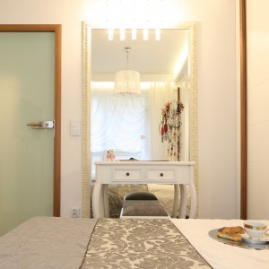 Strefę toaletki wydzielono za pomocą wysokiego lustra, które dodatkowo powiększa przestrzeń. Stylizowana forma mebla doskonale współgra z wystrojem sypialni utrzymanym w eleganckim stylu glamour. Projekt: Małgorzata Mazur. Fot. Bartosz Jarosz.