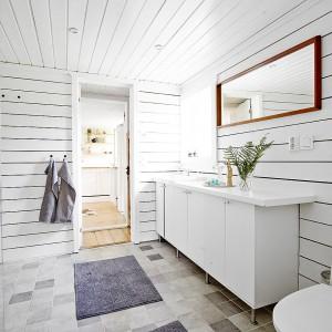 Pomalowane na biało belki są wystarczającą dekoracją samą w sobie, toteż w łazience panuje prostota, bez zbędnych ornamentów czy akcesoriów. Prosta, klasyczna szafka pod umywalką, tradycyjne wc i szklana, niemal niewidoczna strefa prysznicowa chowająca się za delikatnym, prostym szkłem. Jedynymi elementami wybijającymi się na tle aranżacji są płytki podłogowe, niewielki szary dywanik i brązowa rama lustra. Fot. Vastanhem.