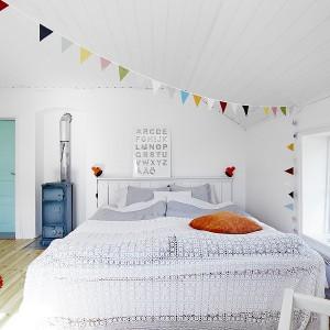 Na drugiej kondygnacji domu zlokalizowano przestronną, jasną sypialnię. Miękkie tkaniny na łóżku i czerwony włochaty dywan w stylu shaggy nadają wnętrzu przytulnego charakteru, mimo iż niemal całe skąpane jest w bieli. Kolorowymi akcentami obok dywanu jest stary błękitny piec i turkusowe drzwi wejściowe. Fot. Vastanhem.