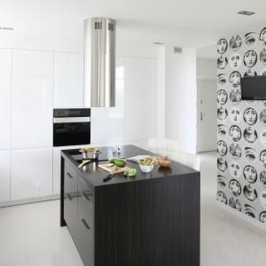 Biała wysoka zabudowa kuchenna kontrastuje z ciemną wyspą w kolorze egzotycznego drewna. Wyspa ma kształt zbliżony do kwadratu.  Nie jest długa, przez co nie zabiera dużo miejsca w kuchni. Jest jednak dość szeroka, dzięki czemu zmieszczono na niej blat i płytkę kuchenną. Na ścianie równoległej do mebla zamontowano niewielki telewizor - możemy gotować i oglądać telewizję. Projekt: Karolina i Artur Urban. Fot. Bartosz Jarosz.